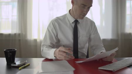 trabalhador de escritório : View of entrepreneur doing paperwork at his desk Stock Footage