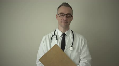 sebész : View of a medical professional holding clipboard Stock mozgókép