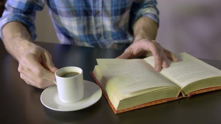 leitor : Dolly shot of man drinking espresso while reading