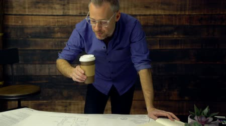kept : Architect drinking coffee marks on engineer prints Stock Footage