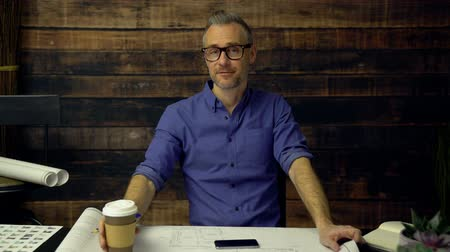 владелец : Dolly shot of a hipster architect drinking coffee and smiling