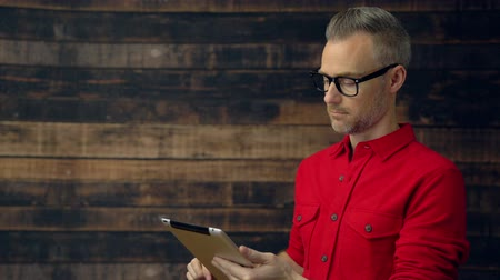 View of a stylish man in red shirt using tablet off center