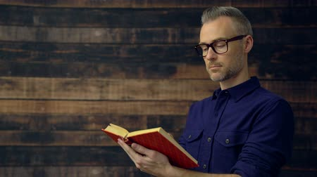 Scene of a man in dark blue shirt reading a book