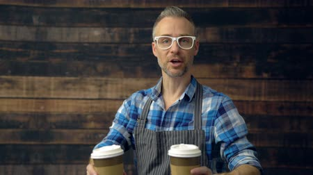 View of hip coffee barista offering two cups to camera
