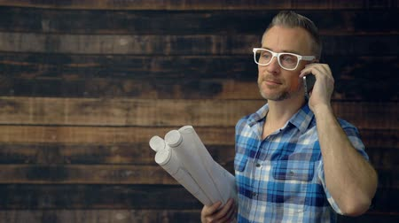 Scene of hipster architect talking on phone looks at camera Stock Footage