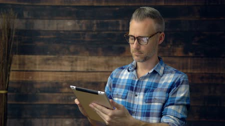 Plaid wearing man is concerned by what he is reading