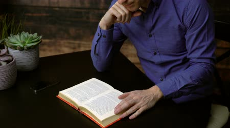 Dolly shot of man reading a hardcover book
