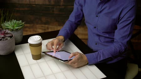 Man using search engine on a mobile tablet sips coffee Stock Footage