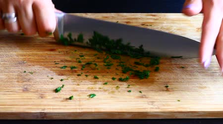 Chef slices parsley with knife on wooden cutting board Stock Footage