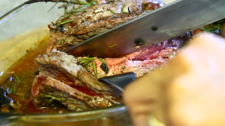 A chef cuts a fillet of cooked meat Stock Footage