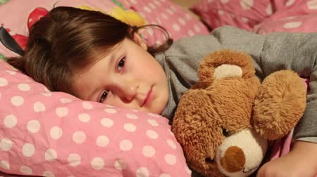 little girl who sleeps with her soft toy and wakes up smiling Stock Footage
