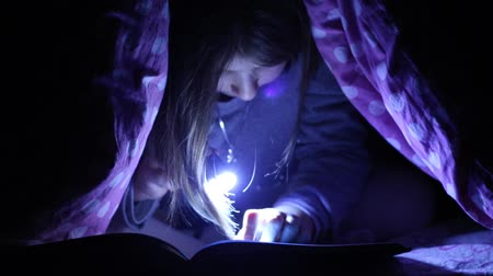 little girl reading a book under blankets with torch