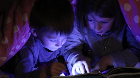 young children reading a book under the blankets with torch
