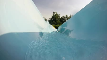 girl coming down from a slide in the pool