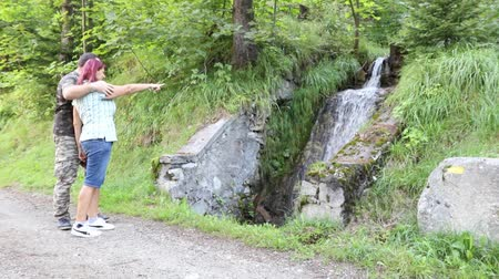 couple stops to watch at the small waterfall in the mountains Stock Footage