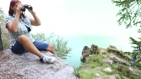 woman watching something with binoculars in the mountains