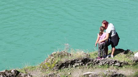mom and daughter look at something on the horizon during a hike to the lake Stock Footage