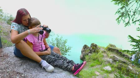 mom and daughter look at something with binoculars