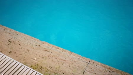 travertine : Side of a pool,  travertine stone edge, washed by small waves of turquoise water lit by sun.