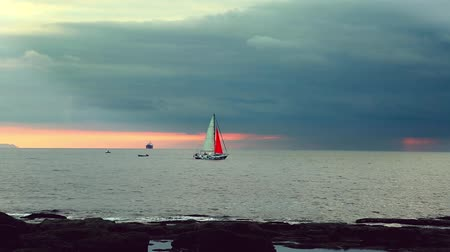 żaglowiec : Colored sailing boat at sunset going to a storm Wideo