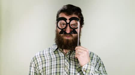 фото : Funny hipster man playing with toy glasses. Its carnival Стоковые видеозаписи