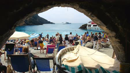 crowded little beach in italy - stone arch - San Fruttuoso abbey - italian riviera - italy