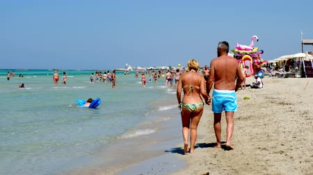 Salento holiday makers walk shore Torre San Giovanni beach crystalline waters Ionian sea Стоковые видеозаписи