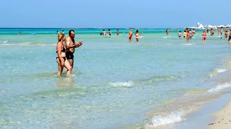 holiday makers : holiday makers walk beach Torre San Giovanni crystalline waters Ionian sea