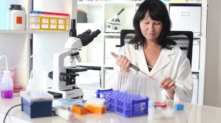 laboratorní plášť : woman with a pipette and a microscope in a lab Dostupné videozáznamy