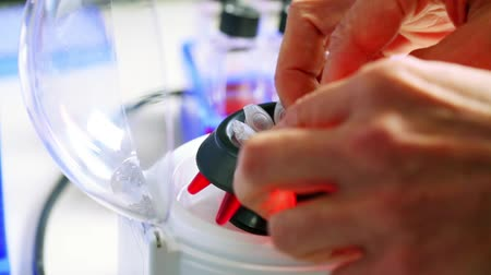 Technician in genetics lab places tubes filled with amniotic fluid and cells into centrifuge