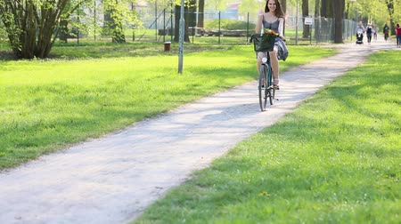 rövid : Young woman in short grey dress with long hair rides a bicycle with basket and flowers tour summer city park look and smile on flowers bouquet