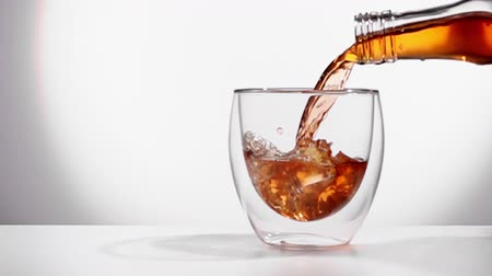 bourbon whisky : drink is poured into a glass in a slow motion.