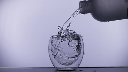 Water is poured into a glass slow motion Stock mozgókép