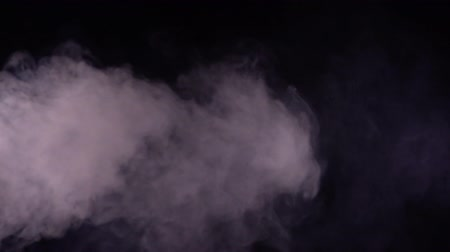 White smoke on black background in slow motion.