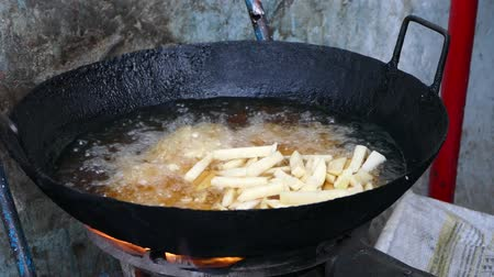french fries in a big frying pan on a street