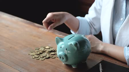 investidor : Business hand putting gold coin into pink piggy bank on brown cement wall background, Saving money for future plan and retirement fund concept. Vídeos