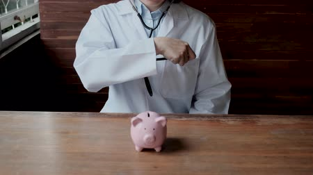 skarbonka : The doctor used a stethoscope to check pink piggy bank, check your financial health for future business plan and Health insurance concept.