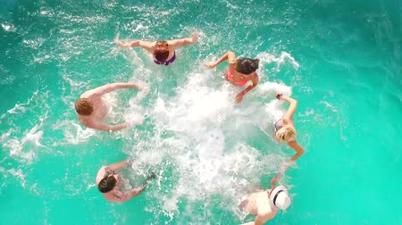 Aerial flight : Happy group of friends enjoying summer pool party splashing in water Стоковые видеозаписи