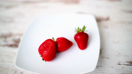 Fresh and ripe strawberries on a wooden table- hd video Vídeos