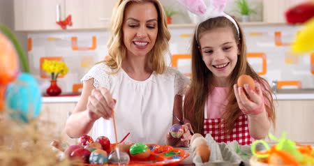 Easter  painting – mother  with daughter  coloring eggs