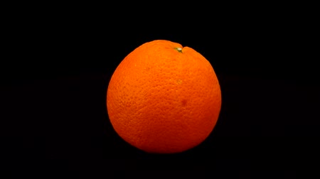 meyve suyu : Orange is spinning on a black background. Stok Video