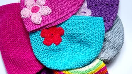 pettyes : Girls colorful crocheted hats rotate on the table Stock mozgókép