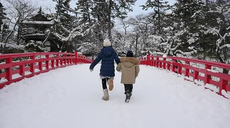 rodzeństwo : Asian children holding hand and running together on red bridge,Hirosaki castle,Japan