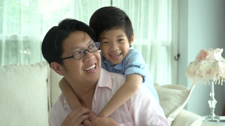 Asian child on a piggy back ride with his father at home slow motion Wideo