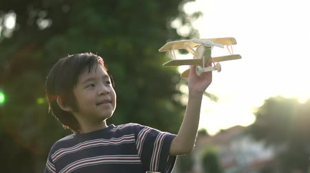 Cute Asian child playing wooden airplane in the park outdoors slow motion