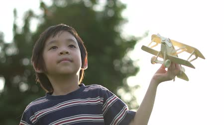 letec : Cute Asian child playing wooden airplane in the park outdoors slow motion