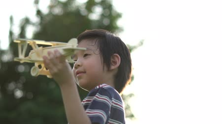 paper airplane : Cute Asian child playing wooden airplane in the park outdoors slow motion