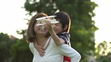 Cute Asian mother and son playing wooden airplane together in the park outdoors slow motion Wideo