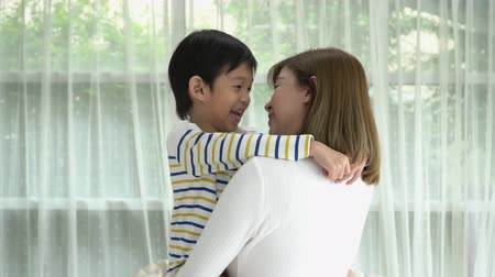 Asian child huging his mother with love at home slow motion Wideo