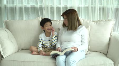 szándékozik : Asian mother and her son reading a book on sofa in living room slow motion